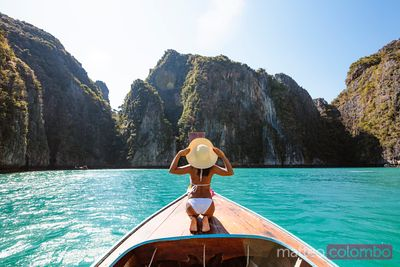 Woman with straw hat on boat prow, Phi Phi islands, Thailand