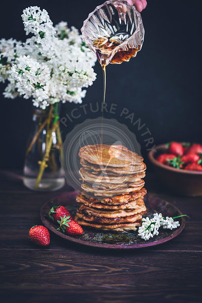 Pouring maple syrup on top of stack of pancakes