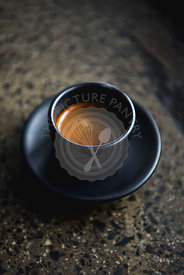 Espresso black coffee in a black cup and saucer on a stone worktop