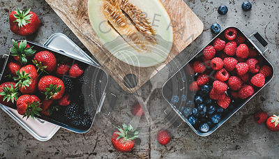 Fresh berries in metal lunchboxes and melon over grey background