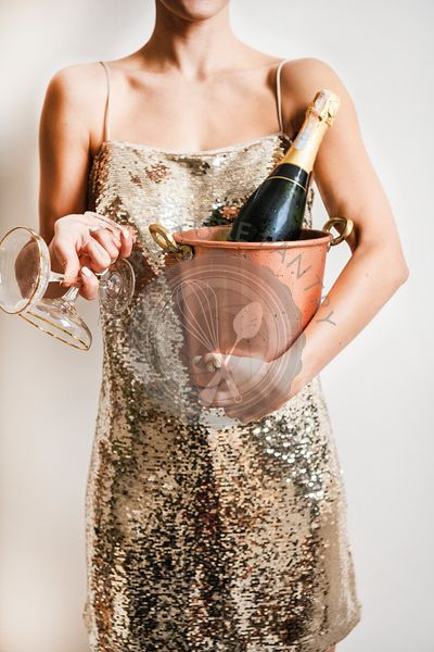 Woman in golden dress holding bucket for champagne and glasses
