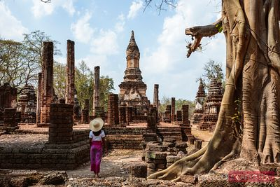 Woman looking at old ruins, Si Satchanalai Historical Park, Thailand