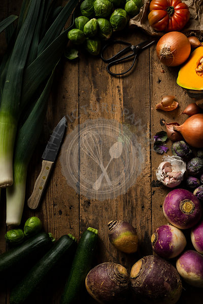 Raw winter vegetables being prepared for soup. They are displayed on a rustic timber background with a wooden handled knife a...