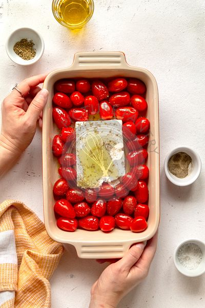 Fresh cherry tomatoes and feta cheese on a baking dish ready to be bake