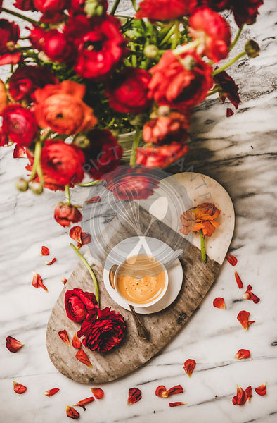 Cup of coffee on serving board and red ranunculus flowers