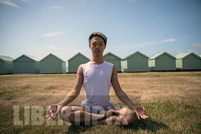 AN IMAGE OF A YOUNG GAY CHINESE MAN DOING EXERCISE AND YOGA OUTDOORS.