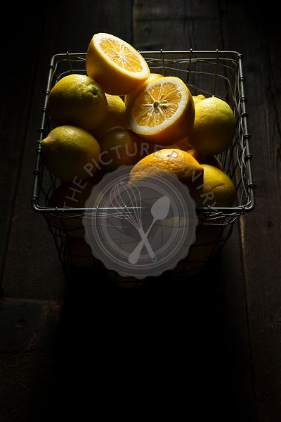 Home grown lemons in a square wire basket, on a rustic wooden ba