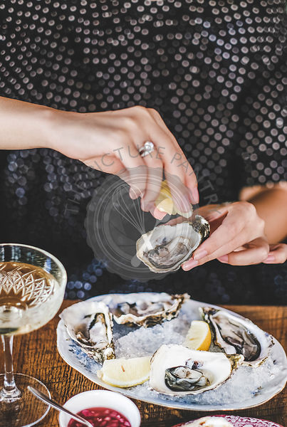 Woman squeezing lemon juice to fresh Irish oysters in restaurant