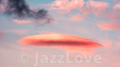 Orange, lenticular cloud and pastel blue sky in background.