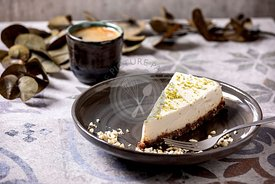 Raw vegan cheesecake with lime zest and cashew nuts on plate