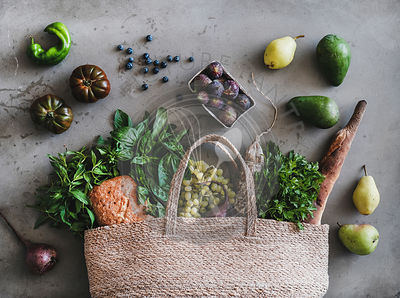Flat-lay of eco-friendly bag with fresh produce, bread and sausage