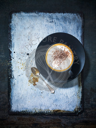 A cappuccino in a blue ceramic cup and saucer against a chalk and grey background.