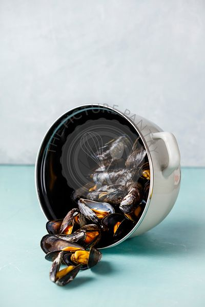Pot of steamed mussels on blue background