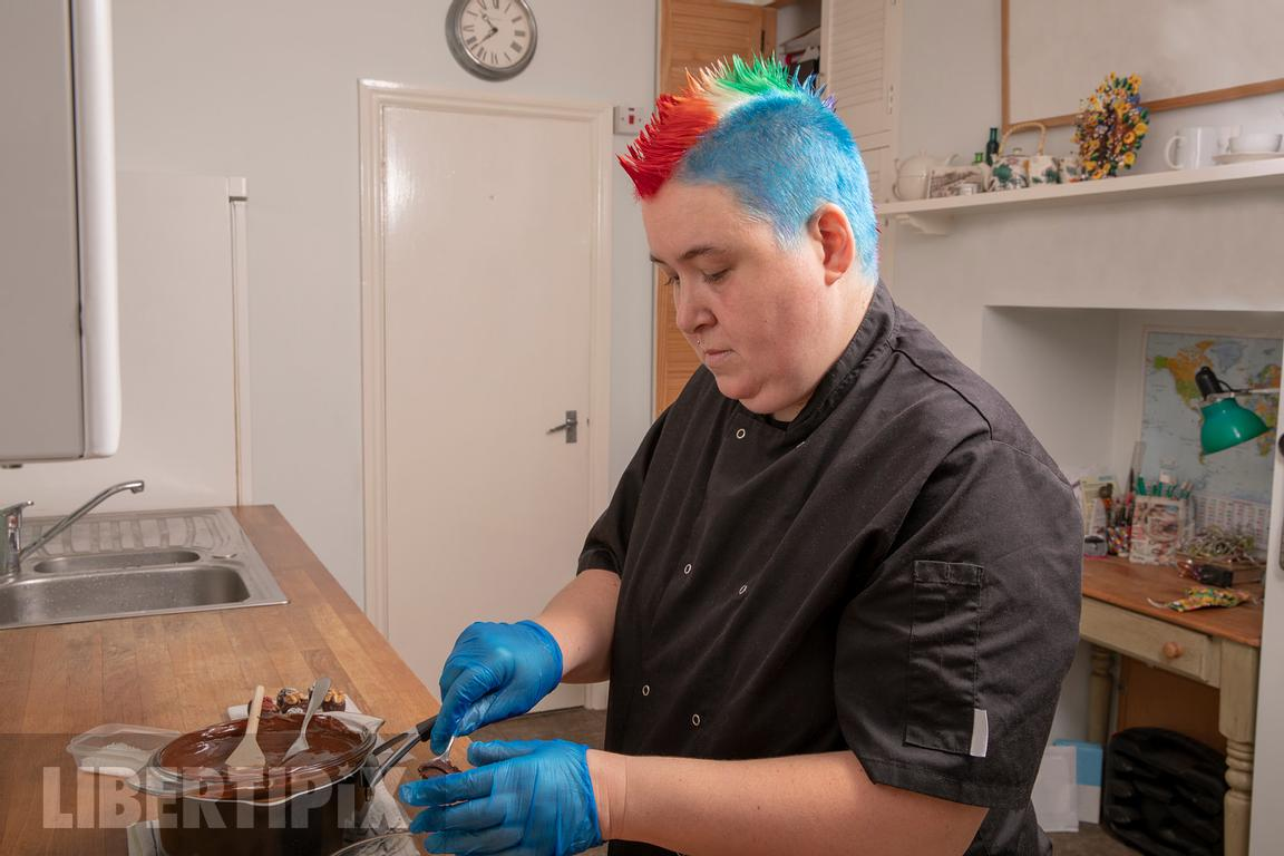 One non-binary person, making food, wearing a chef''s outfit-LGBTQ+ stock photos