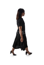 A semi-silhouette of a woman, walking in a black dress - shot from eye level.