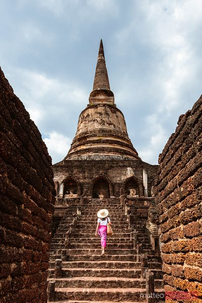 Female tourist walking on stairway, Si Satchanalai, Thailand