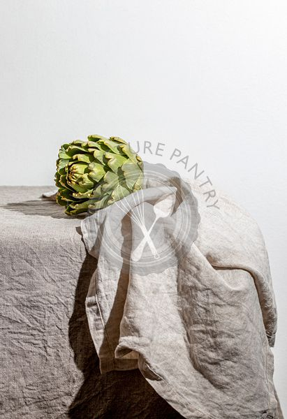 Artichoke on the table covered with a gray linen tablecloth.