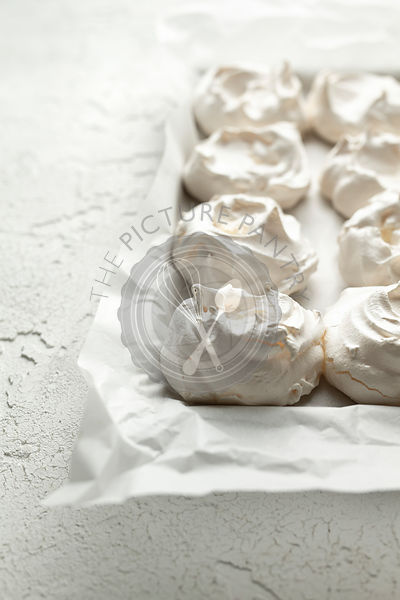 Meringues on baking parchment, on a white textured background.