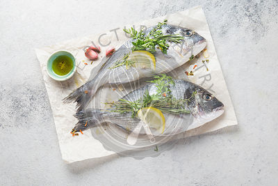 Uncooked sea bream or dorada with herbs and lemon