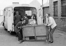 #75013  Bill Murphy (white jacket) and John Howard lifting table.  Moving equipment and books into the building, Liverpool Fr...