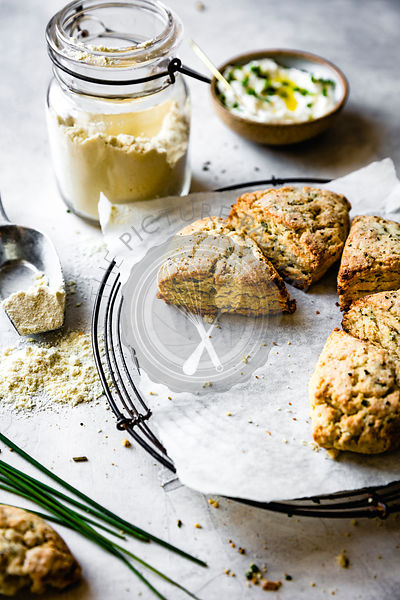 Cheese and herb scones beside a jar of oat flour.