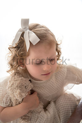 A litle girl with a suitcase and teddy bear – shot from mid level.
