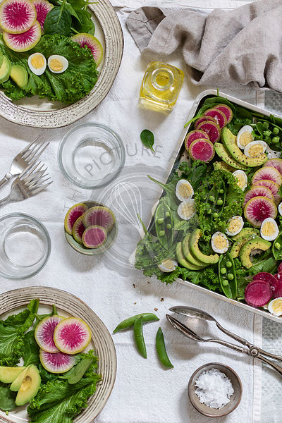 Mustard salad with watermelon radishes, green peas, avocado and quail eggs
