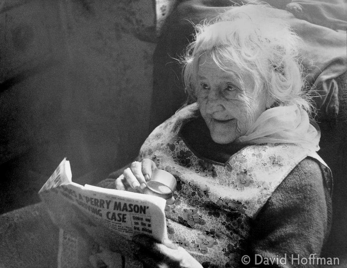 Impoverished pensioner reading newspaper