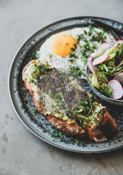 Avocado toast, fried egg and salad with radish