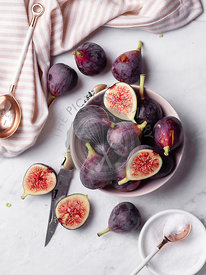 A bowl of ripe, purple figs on a white marble countertop surrounded by a striped napkin, rose gold spoons, and a small bowl o...
