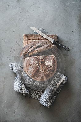 Freshly baked sourdough bread on wooden board, vertical composition