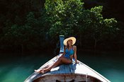 Young woman in swimwear sitting on wooden boat prow, Thailand