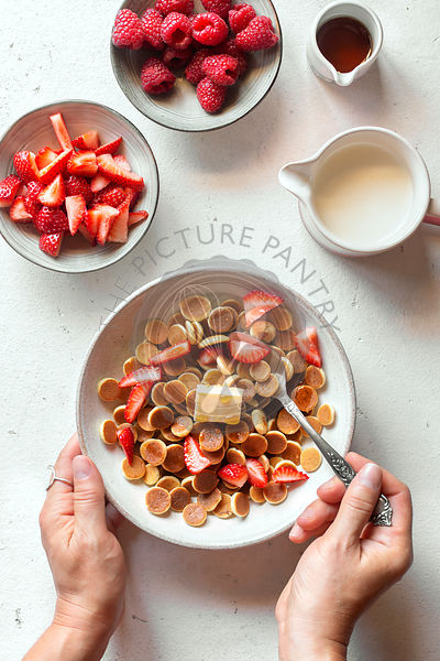Pancake cereal with strawberry in a bowl over a white background