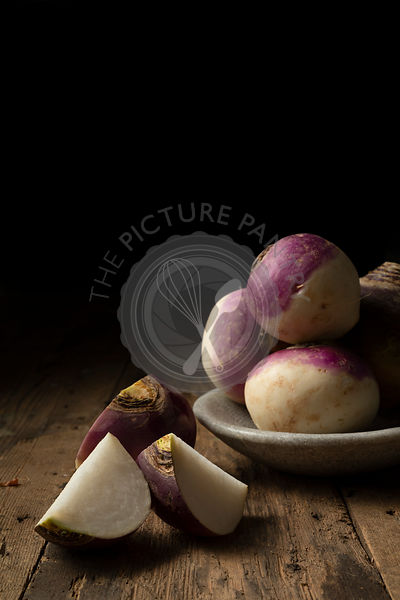 Raw whole and cut turnips in a bowl on a rustic wooden surface.