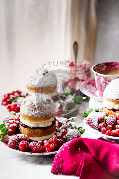 Victoria Sponge Cake with raspberry jam and whipped cream , generously sprinkled with powdered sugar , served with fruits.