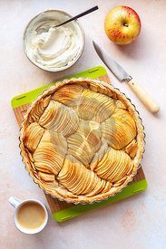 Apple tart with whipped cream and a cup of coffee on the table.