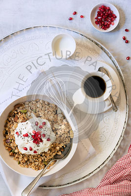 Healthy breakfast bowl of muesli, yoghurt and pomegranate seeds served with a jug of milk and a cup of coffee.