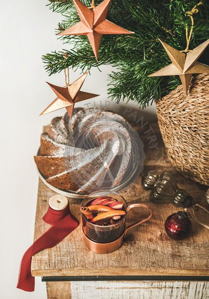 Cup of mulled wine and Christmas bundt cake over counter