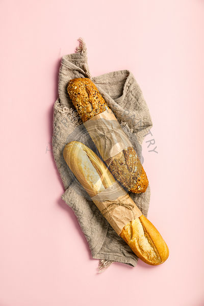 Top view of white and wholegrain baguettes over pink background