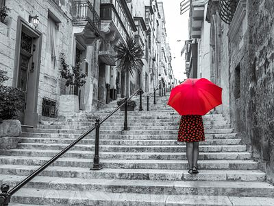 Tourist with an Umbrella on steps through buildings, Valletta, Malta