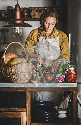 Young woman in apron cooking vegetables preserves in kitchen