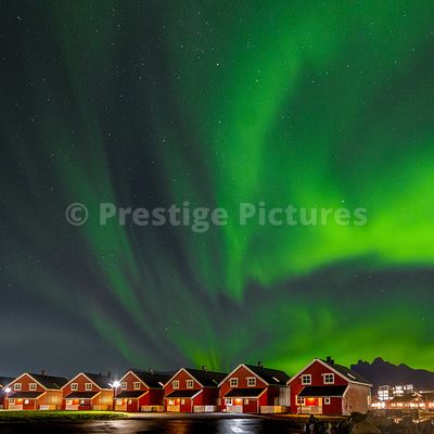 Northern Lights in the sky over Norwegian red houses with lights reflecting in the harbour waters in Svolvaer, Norway