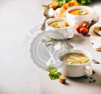 Pea, tomato, vegetable soups and ingredients on concrete background