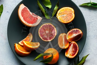 Fresh citrus fruit on a black plate