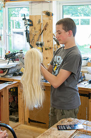 #72986,  Lad playing with a wig his mother had lent him, carpentry workshop, Summerhill School, Leiston, Suffolk. The school ...