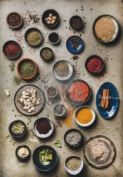 Flat-lay of colorful spices in bowls over grey concrete background