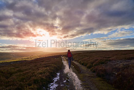 A hiker centre frame walking straight towards a sunset on open heather moors at Edmundbyers.