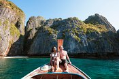 Adult couple on boat prow, Maya bay, Phi Phi islands, Thailand