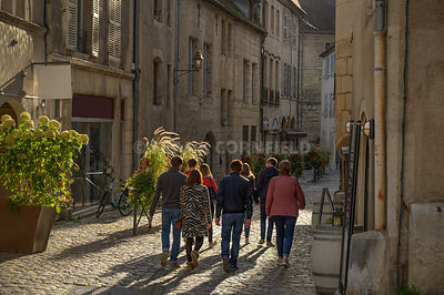 A group of unidentfied people walkin in an old street in the city of Dole in France.