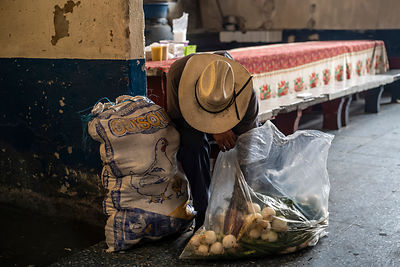 A man collect fallen onions in a market in Guatemala City, Guatemala